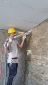 Spraying Diathonite into first floor wall junctiom
